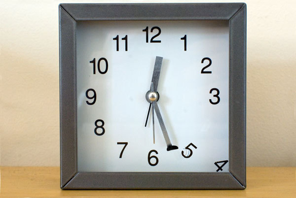 clock with hands that are kicking the numerals away
