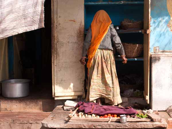 Woman in Bundi in Rajasthan, India with vegetables set out for sale