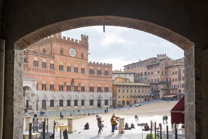 View through an archway onto the Piazza del Campo in Siena