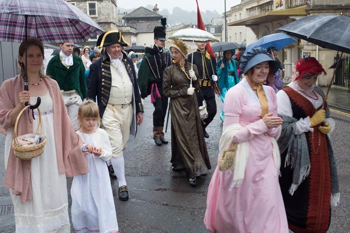 People in Regency costume in procession during Jane Austen Week in Bath