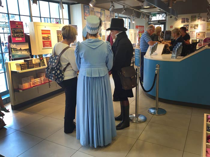 People-in-Regency-costume-in-the-Tourist-Office-during-Jane-Austen-Week in Bath