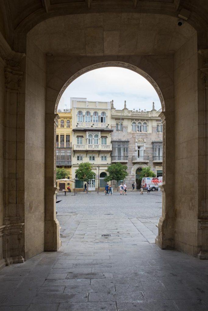 A view through an archway onto  Plaza de San Francisco, Seville